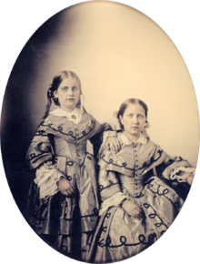 An oval, framed photographic portrait of two young girls dressed in elaborate Victorian-era gowns