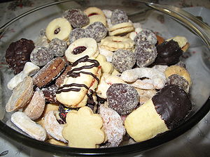 Cookie - A dish of assorted cookies, including sandwich cookies filled with jam.
