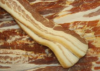 Uncooked pork belly bacon strips displayed behind glass in Gorman's Butcher Shop in Pine Island, Minnesota