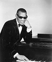 A dark-skinned man wearing dark glasses and a tuxedo, leaning on a piano