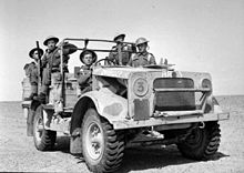 A military vehicle in the desert with five soldiers aboard.
