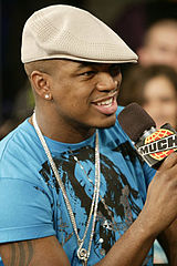 Ne-Yo wearing a beige cheese-cutter hat, blue t-shirt and a necklace, speaking into a microphone.