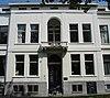foto van Herenhuis, met gepleisterde lijstgevel waarvan de middenpartij op de verdieping een getoogde loggia met balkon op consoles heeft