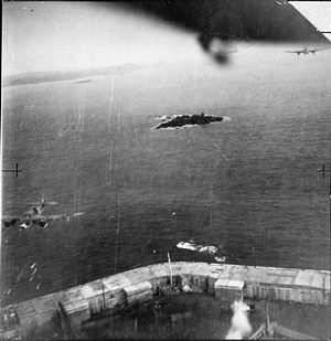 Saint Peter Port Harbour - A low-level oblique photograph taken from one of 3 Bristol Beauforts of No. 86 Squadron RAF, attacking shipping in St Peter Port, Guernsey. The aircraft are passing over St Julian's Pier at its junction with White Rock Pier: bombs can be seen falling from the aircraft in the left-hand corner, which was itself nearly hit by bombs dropped from the photographing aircraft (seen exploding at the bottom).