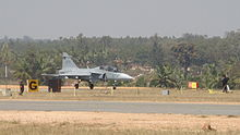 Jet aircraft in the distance preparing to take off from rural airport surrounded by green trees