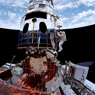 STS-61 - Musgrave and Hoffman prepare to install the new Wide Field and Planetary Camera, visible on the payload bay sill.