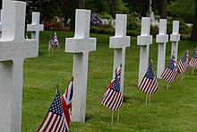 White grave markers with flags