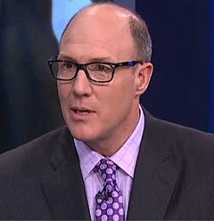 Head and shoulders photograph of Pioli wearing a dark blue suit with a purple patterned tie and black eyeglasses