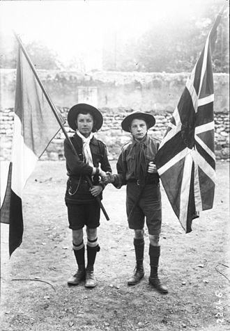 Entente Cordiale - French and British scouts shaking hands with their respective national flags. 1912