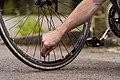 Screwing on tyre pressure inlet valve cap on bicycle.jpg