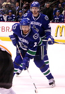 Two twin ice hockey players in ready positions on the ice, lining up for a faceoff. One player in the forefront, is leaning forwards, putting his weight on his stick on the ice, while the other player in the background is standing upright. They are both looking intently forward. They wear blue jerseys with white trim and blue visored helmets.