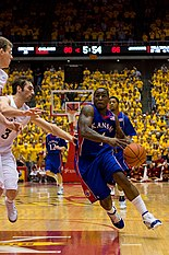 A person wearing a blue-colored basketball uniform dribbling a basketball running against another person wearing a white basketball uniform.