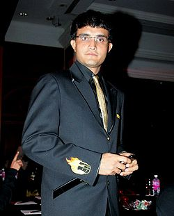 Sourav Ganguly wearing glasses stares directly at the camera. He is wearing a black suit and a gold tie. The man's right arm is facing the camera. The arm has a small picture of a helmet engulfed with fire.