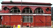 "A two-storey red-glazed building with a single rectangular window on the lower floor and three large semi-circular windows on the upper floor flanked by two small circular windows. A white band between the floor levels displays ""South Kensington station""."