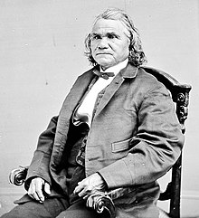 Formal photograph of a seated Stand Watie, in European dress