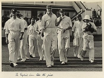 A group of ten men are walking onto a grass playing field in front of a building which has spectators sitting in front. The men are all dressed in white shirts and trousers while most of them are wearing cricket caps. One man has pads and wicketkeeping gloves on.