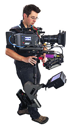 The larger Steadicams are designed to support 35mm film cameras, digital cinema cameras, and IMAX cameras. Steadicam Operator John Fry with Master Steadicam & Arri Alexa camera.jpg