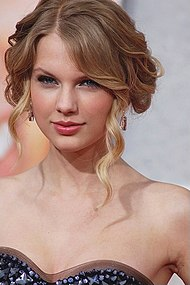 Taylor Swift, wearing a strapless dress, looks directly at the camera. Her hair is tied back, with a few curly tendrils loose
