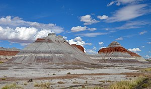 Conical rock formations showing horizontal banding in red, white, and shades of grey