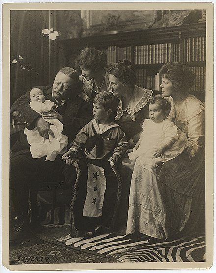 Seated, left to right, are Archibald Bulloch Roosevelt, Jr., Theodore Roosevelt, Grace Stackpole Lockwood Roosevelt, Richard Derby, Jr., Edith Kermit Carow Roosevelt, Edith Roosevelt Derby Williams, and Ethel Carow Roosevelt Derby. Richard Derby Jr. is holding a service flag with three stars. The stars symbolize three of Roosevelt's sons, Quentin, Archie, and Theodore Jr., who served the United States in battle. (Theodore Roosevelt with His Family at Sagamore Hill) (13566050043).jpg