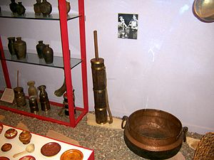Yak butter - Butter churn, displayed with Tibetan kitchen items at the Field Museum. Note the strap for carrying it and its small size, adaptations to nomadic use.