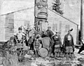 Tlingit men and boy in traditional costumes standing in front of totem pole, Fort Tongass, Dec 14, 1887 (AL+CA 621).jpg