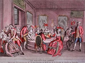 Animal magnetism - Baquet. Interior view: Drawing room scene with many people sitting and standing around a large table; a man on a crutch has an iron band wrapped around his ankle; others in the group are holding bands similarly; to the left, a man has hypnotized a woman. (1780)