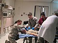 U.S. Air Force Master Sgt. Erica Jasper, left, Staff Sgt. Caitlyn Thomason, center, and Maj. Marlo Repeta, in red, a medical response team assigned to the 79th Medical Wing (MDW), provide care for a simulated 130110-F-MW123-002.jpg