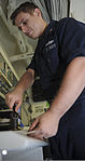U.S. Navy Legalman 2nd Class Pahl Sayeksi certifies a document aboard the aircraft carrier USS Nimitz (CVN 68) Aug. 21, 2013, in the Gulf of Oman 130821-N-AZ866-136.jpg