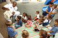 US Navy 030605-N-0106C-003 Gas Turbine Systems Technician 2nd Class Clieveral A. Troxler assigned to Naval Station Pearl Harbor, reads a book to a group of three-year-olds at the Naval Station Child Development Center (CDC).jpg