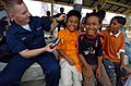 US Navy 050222-N-8629M-319 Hospitalman Joshua Scott, assigned to the Military Sealift Command (MSC) hospital ship USNS Mercy (T-AH 19), entertains Indonesian children with his portable compact disc player.jpg