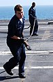 US Navy 050513-N-8148A-138 Arresting gear crew members, Airman Greg Reichard, left, and Aviation Boatswain's Mate Airman Joseph Mustin, assigned to the V-2 Department, race to reconnect a cross deck pendant.jpg