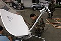 US Navy 060601-N-9076B-012 Navy Petty Officer 2nd Class Michael Orta of Los Angeles assembles a high-frequency satellite used for communications at Zamboanga Medical Center.jpg
