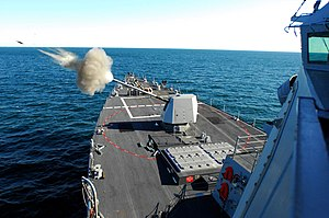 "USS Forrest Sherman (DDG-98) - USS Forrest Sherman (DDG 98) in 2007, test firing her new 5""/62 caliber Mark 45 Mod 4 gun, located forward of her  32-cell missile pack module."