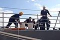 US Navy 070304-N-4965F-005 Sailors assigned to guided missile cruiser USS Bunker Hill (CG 52) handle lines as she moors pierside Naval Station Pearl Harbor.jpg