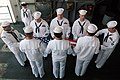 US Navy 070822-N-3136P-027 First class petty officers selected for chief petty officer fold a flag during a ceremony aboard USS Kitty Hawk (CV 63) for the Battle of Leyte Gulf.jpg