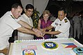 US Navy 080617-N-0209M-005 Capt. William A. Kearns, Edsel T. Custodio, Kristie A. Kenney and Capt. Crispin P. Mercado cut a cake together during a reception ceremony aboard Mercy.jpg