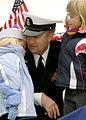 US Navy 081202-N-6700F-087 Storekeeper Senior Chief Doug Fern hugs his daughters after departing the amphibious assault ship USS Kearsarge (LHD 3).jpg