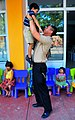US Navy 090220-N-4774B-015 Gunner's Mate 3rd Class Joahn Tinjaca entertains a child during a Project Handclasp community relations event.jpg