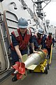 US Navy 090304-N-9123L-006 Sailors aboard the guided-missile destroyer USS John S. McCain (DDG 56) maneuver a recovered training torpedo after completing a torpedo exercise.jpg