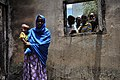 US Navy 090812-N-0506A-273 Zamzam Ahmed Dinbil stands holding her child in the burned remains of her home in Djibouti.jpg