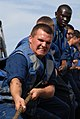 US Navy 090924-N-1688B-265 Seaman Recruit Travis Cliborne, from Richmond, Va., heaves a line with his team during a replenishment at sea aboard the guided-missile destroyer USS Cole (DDG 67).jpg
