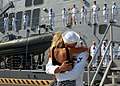 US Navy 100901-N-5292M-074 Boatswain's Mate 2nd Class Brandon Carney receives the traditional first kiss from his wife during a homecoming celebration for the guided-missile destroyer USS Cole (DDG 67).jpg