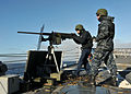 US Navy 110606-N-NL541-124 Logistics Specialist 3rd Class Mickey Thiele fires a .50 caliber machine gun while Seaman Michael Trusik maintains radio.jpg