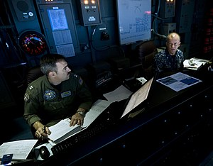 US Navy 120107-N-MD252-180 Lt. Brian Snook, left, and Cmdr. David Schlesinger discuss flag operations in the tactical flag command center aboard th.jpg
