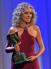 Valeria Golino holding her second Volpi Cup in 2015, wearing a dark red dress while holding a golden trophy.