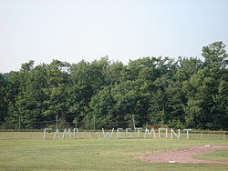 "Green field with green trees in the background. Large, wooden letters in the foreground spell ""C A M P  W E S T M O N T."""
