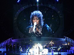Houston performing on stage. Behind her is a screen where she is shown wearing a white outfit with a black overcoat and performing.