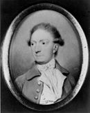 Black and white print depicts a clean-shaven man with his hair rolled over his ears in late 18th century style. He wears a coat over a frilled white shirt.