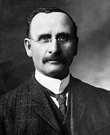 A photographic head and shoulders portrait of a moustached man wearing a three piece suit and round glasses